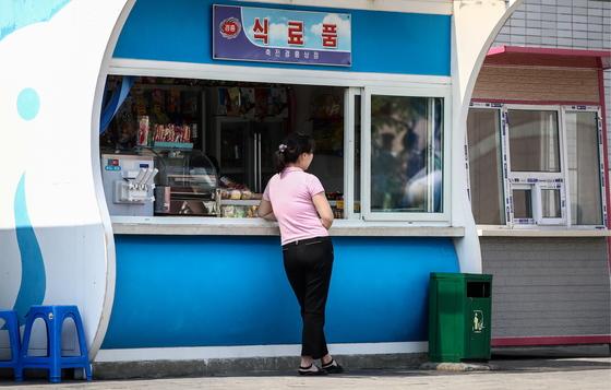 지난달 31일 평양 길거리 매점에서 손님을 기다리는 판매원. [타스=연합뉴스]