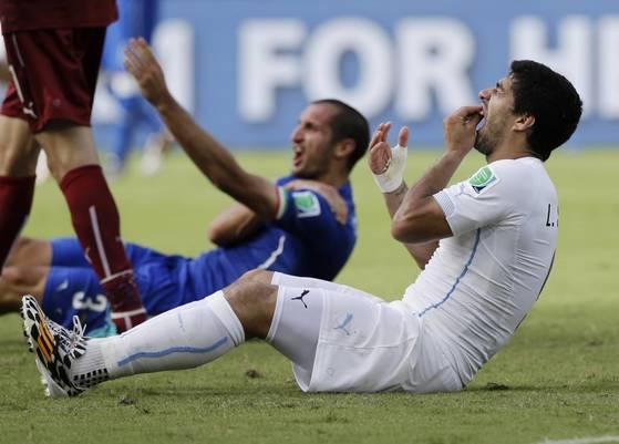브라질 월드컵 본선 경기에서 우루과이 공격수 수아레스(오른쪽)가 이탈리아 수비수 키엘리니(가운데)의 어깨를 깨문 뒤 치아에 통증을 호소하고 있다. [AP=연합뉴스]