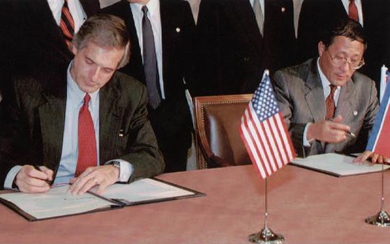 1994년 10월 21일 당시 로버트 갈루치 미국 핵대사(왼쪽)와 강석주 북한 외교부 부부장이 스위스 제네바에서 북미 고위급회담의 기본합의문에 서명하고 있다. 제네바합의는 북핵 폐기를 위한 과정과 일정, 그리고 보상이 상세하게 규정됐지만 성과를 내지 못했다.[중앙포토]