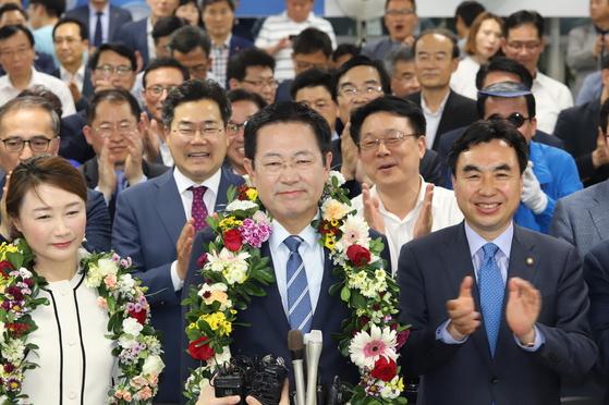 박남춘 인천시장 후보자가 당선 확실하다는 언론보도에 지지자들이 건넨 꽃다발을 목에 걸고 환하게 웃고 있다. [사진 박남춘 후보 캠프 ]