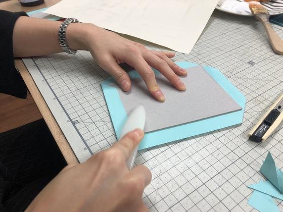하드커버에 색지를 씌우는 과정.