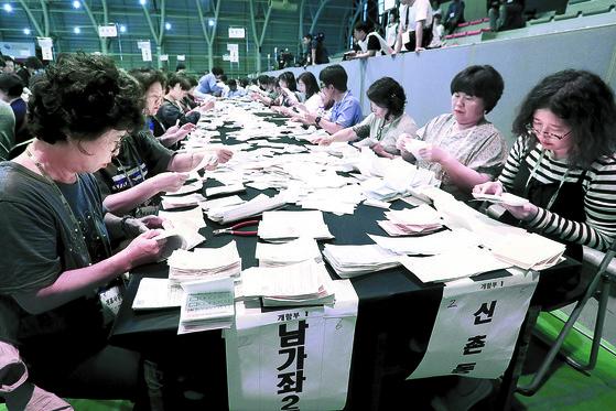 제7회 전국동시지방선거가 13일 오후 6시 종료돼 전국 254개 개표소에서 개표작업이 진행됐다. 이날 서울 서대문구 명지전문대 체육관에서 개표원들이 투표용지를 분류하고 있다. [장진영 기자]