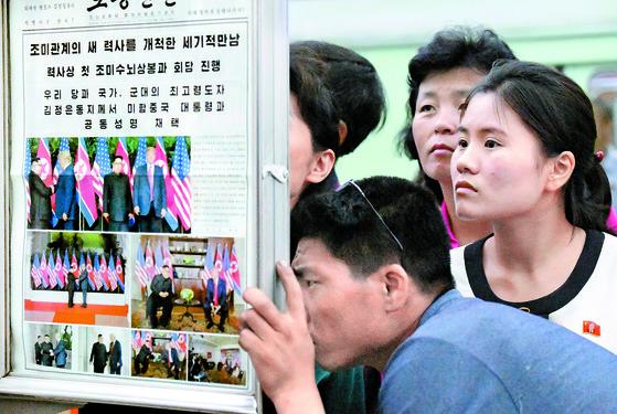 북한 주민들이 13일 평양 지하철역에서 노동신문에 실린 김정은 국무위원장과 도널드 트럼프 대통령의 정상회담 관련 기사를 살펴보고 있다. [교도=연합뉴스]