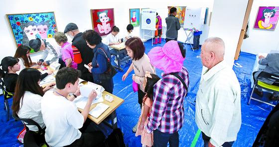 부산시 민락동 미광화랑에 마련된 투표소를 찾은 유권자들이 13일 투표하고 있다. [송봉근 기자]