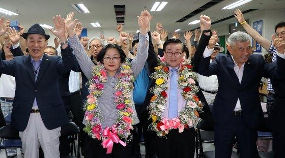 윤일규 더불어민주당 천안병 국회의원 당선인(오른쪽 둘째)이 13일 충남 천안 선거사무실에서 꽃목걸이를 목에 건 채 두 손을 들어보이고 있다. [뉴스1]