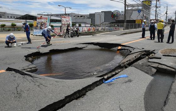 근로자들이 오사카 타카쓰키 지역에서 강진으로 도로에 생긴 웅덩이를 살피고 있다. [지지통신=연합뉴스]