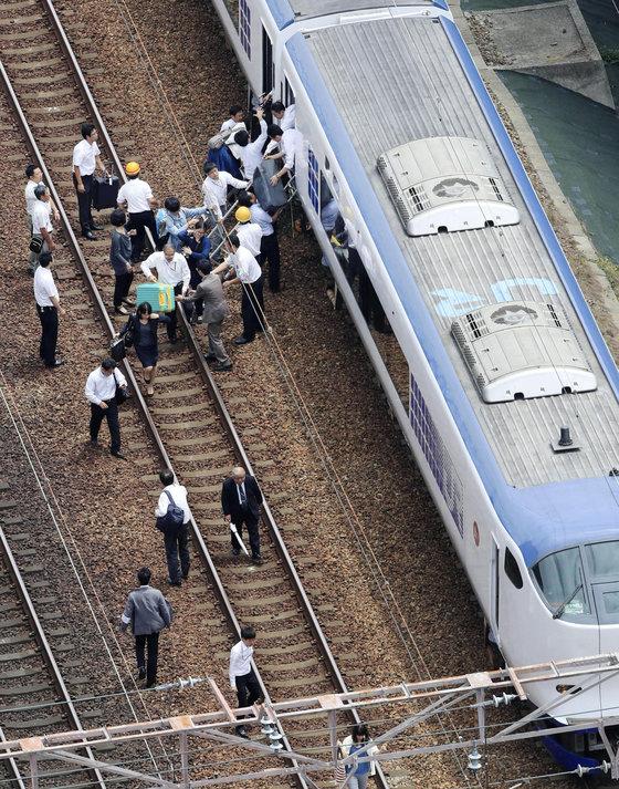 오사카 지역 강진으로 타카스키에서 열차 운행이 중단되자 승객들이 걸어서 이동하고 있다.[교도=연합뉴스]