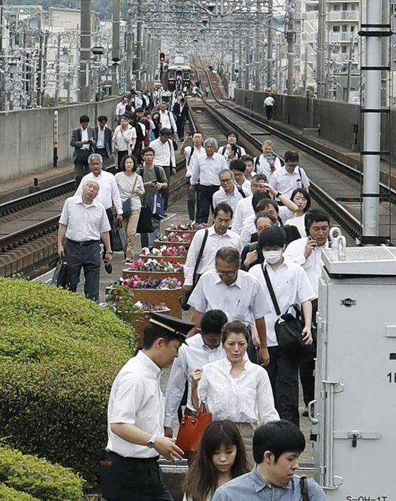 오사카 지역 강진으로 이케다에서 열차 운행이 중단되자 승객들이 걸어서 이동하고 있다.[교도=연합뉴스]