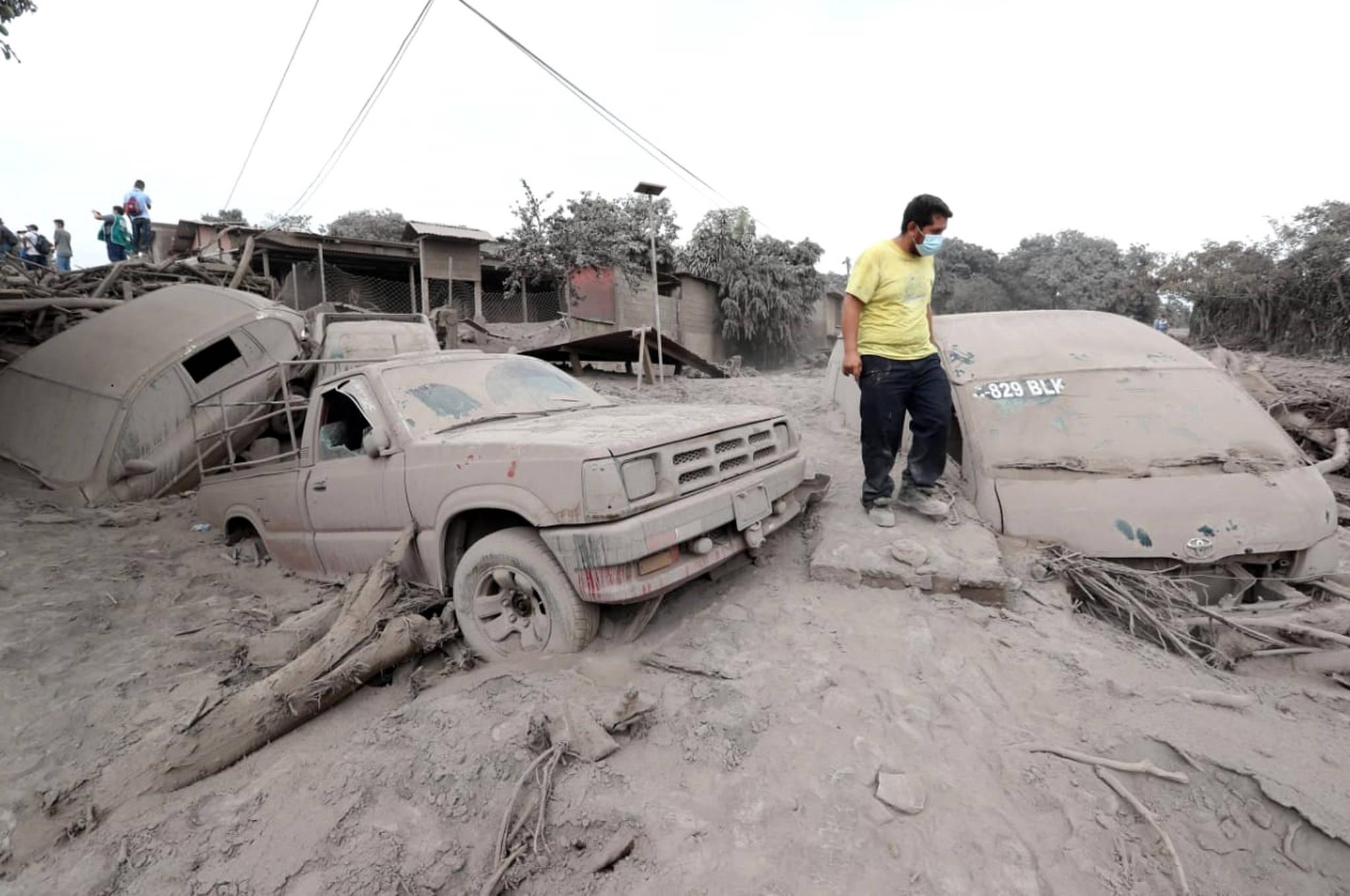 콰테말라 푸에고 화산 폭발로 피해를 입은 차량을 지난 5일 현지 주민이 둘러보고 있다. [Xinhua=연합뉴스]