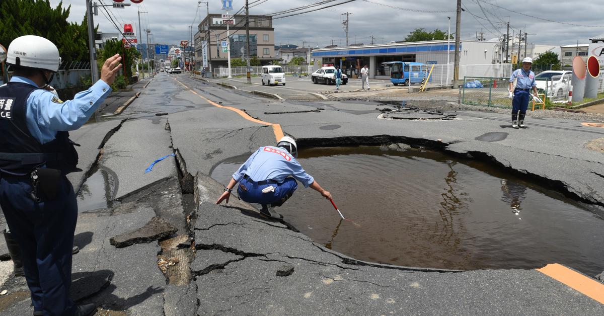 18일 오사카 현 다카쓰키시에서 발생한 지진으로 인한 도로 파손 사고를 점검하고 있다. [EPA=연합뉴스]