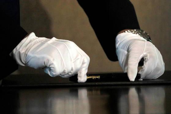 지난 6월 12일 열린 북미 정상회담에서 북측경호원이 흰장갑을 끼고 김정은 위원장이 사용할 펜을 꼼꼼하게 닦고 있다. [로이터=연합뉴스]