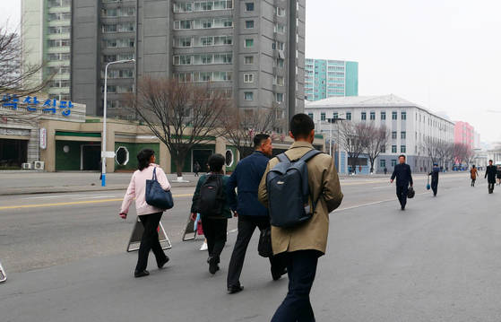 평양 고려호텔 앞 도로에서 시민들이 출근하고 있다.