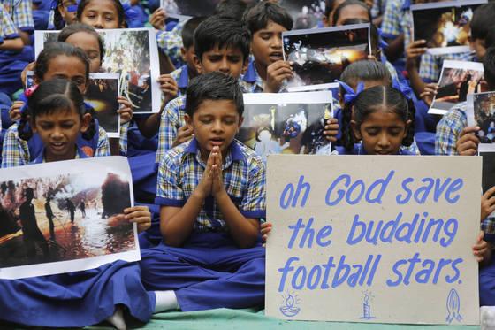 지난 9일 인도 아흐마다 바드의 한 학교 학생들이 태국 북부 동굴에 갇혀있는 유소년 축구팀 선수들과 코치의 무사 구조를 위해 기도하고 있다. [AP=연합뉴스]