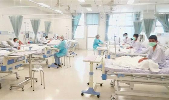 11일(현지시간) 처음으로 공개된 태국 축구팀 소년들의 병원 내 모습. 전날 코치를 비롯한 13명 전원이 무사히 구조돼 귀환한 이들은 검진 및 치료 등을 위해 격리실에서 마스크를 쓴 채 생활하고 있다. [로이터=연합뉴스]