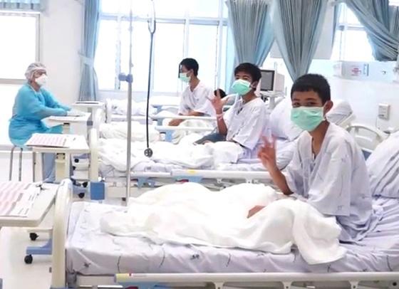 11일(현지시간) 처음으로 공개된 태국 축구팀 소년들의 병원 내 모습. 한 소년이 카메라를 향해 승리의 V 사인을 하고 있다. 전날 코치를 비롯한 13명 전원이 무사히 구조돼 귀환한 이들은 검진 및 치료 등을 위해 격리실에서 마스크를 쓴 채 생활하고 있다. [EPA=연합뉴스]
