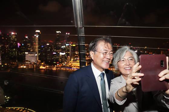 싱가포르를 국빈 방문 중인 문재인 대통령이 12일 밤 싱가포르의 상징이 된 마리나 베이 샌즈 전망대를 방문해 강경화 외교부 장관과 휴대전화로 사진을 찍고 있다. [연합뉴스]