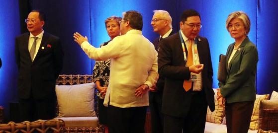 지난해 8월 8일 오전(현지시간) 아세안 50주년 기념식에서 리용호 북한 외무상(왼쪽)이 홀로 서 있다. 강경화 외교부 장관(오른쪽)은 다른 참가자와 얘기를 하고 있다. 연합뉴스