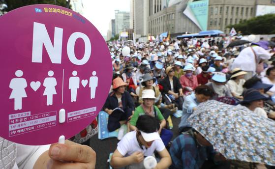 14일 오후 서울 중구 덕수궁 옆 세종대로에서 '동성애축제반대 집회'가 열렸다. 한 집회 참가자가 노(NO)라고 적힌 부채를 들고 있다. [뉴시스]