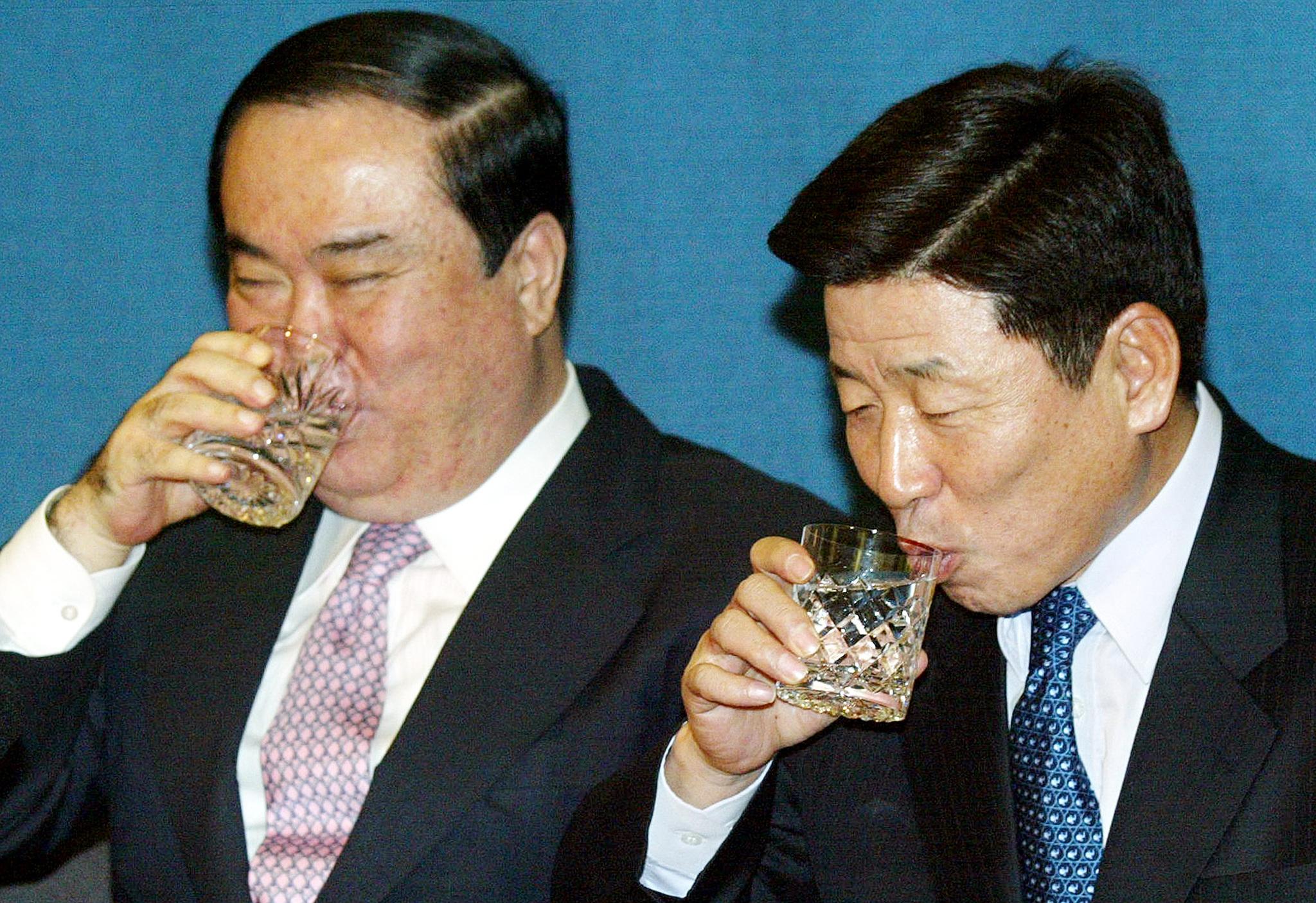 문희상 전 대통령 비서실장(左)과 유인태 전 정무수석이 2004년 청와대 춘추관에서 총선 출마 기자간담회를 하던 도중 물을 마시고 있다. [중앙포토]