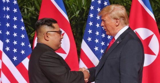 역사적 첫 북미정상회담이 열린 12일 오전 회담장인 카펠라 호텔에 북한 김정은 위원장과 미국 트럼프 대통령이 회담을 위해 만나고 악수를 나누고 있다. [싱가포르 정부 제공]