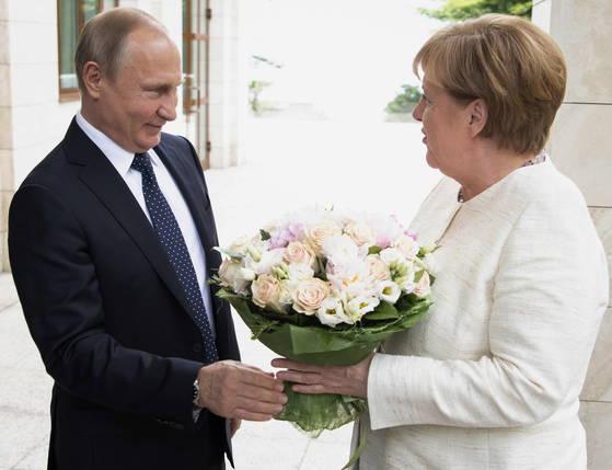 독일의 앙겔라 메르켈 총리(오른쪽)이 지난 18일 러시아 남부 소치에서 블라디미르 푸틴 러시아 대통령을 만나 꽃다발을 받고 있다. [로이터=연합뉴스]