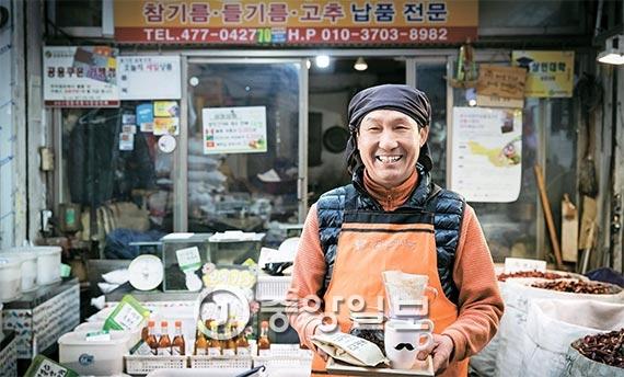 서울 길동 복조리시장의 성창기름집 육근목 사장이 자신이 직접 볶은 원두와 커피를 들고 서 있다. 육 사장 뒤로 보이는 가게는 그가 26년간 운영한 방앗간이자 커피 로스팅 가게다. 참깨·들깨를 주로 볶아 온 그는 지난해부터 커피 원두도 볶는다. [사진 장진영 기자]
