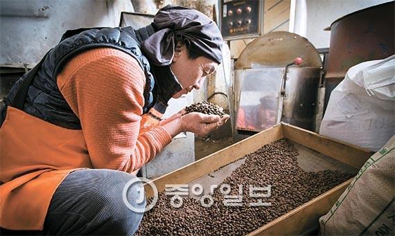 갓 볶은 커피 원두를 채에 고르게 펴서 식히면서 원두 향을 맡고 있는 육 사장. [사진 장진영 기자]