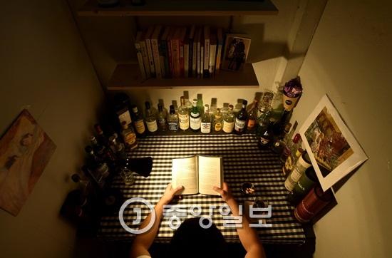 서울 연희동에 위치한 `책바`에서 한명씩 온 손님들이 책을 읽으며 술을 즐기고 있다. [사진 중앙일보]