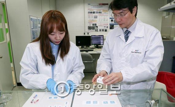 조용훈 교수(오른쪽)와 김세정 연구원이 종이를 기판으로 한 반도체 광소자를 바라보고 있다.