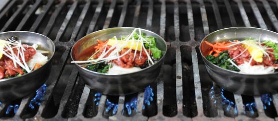 '비빈 밥'에 고명과 육회를 얹은 뒤데워 먹는 익산 진미식당 육회비빔밥.