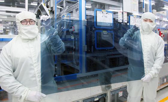 지난 17일 경기도 파주 LG디스플레이 공장에서 연구원들이 나노입자를 바른 편광판을 들어 보여주고 있다. 이 편광판은 액정표시장치(LCD) 패널에 붙여진다. [사진 LG디스플레이]
