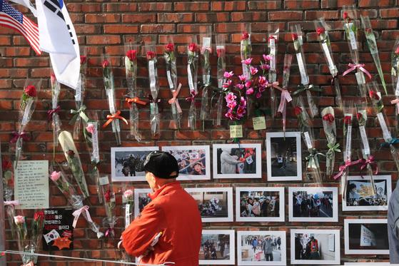 태극기를 든 한 시민이 19일 박근혜 전 대통령의 서울 삼성동 자택 담장에 붙어 있는 장미와 사진 등을 살펴보고 있다. 박 전 대통령은 이날 변호인들과 함께 21일로 예정된 검찰 조사에 대비했다. [사진 최정동 기자]