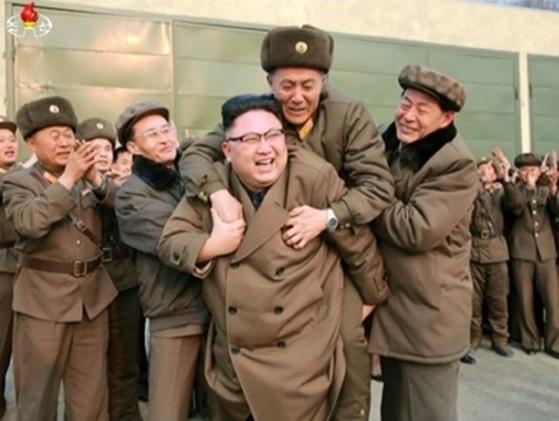김정은이 지난 19일 미사일 엔진 분출 시험 뒤 관계자를 업어주고 있는 모습. [조선중앙TV 캡쳐]