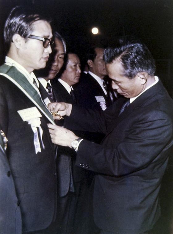 72년 11월 김우중 회장(오른쪽 사진 왼쪽)이 박정희 당시 대통령으로부터 금탑산업훈장을 받고 있다. [사진 대우세계경영연구회]