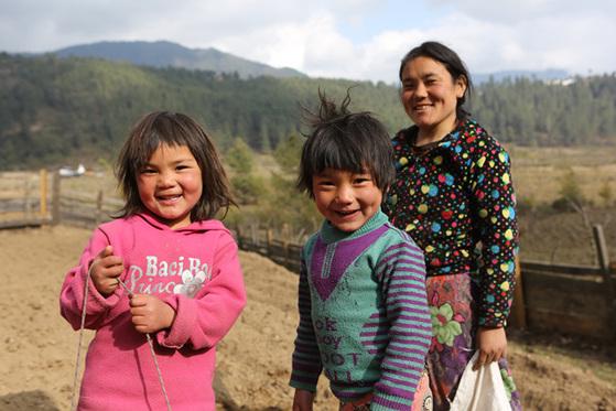 부탄 고산마을 포지카에서 감자 심는 아낙과 그의 아들딸.