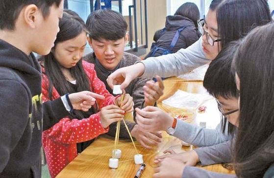 마시멜로를 올리기 위해 삼각 다리의 형태로 스파게티면을 세워 안정성을 확보한 참가자들.