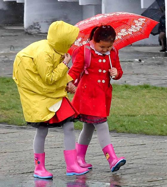 5일 오전 평양 시내에서 나이키 운동화를 신은 한 여학생(가운데)이 친구들과 함께 우산을 쓰고 학교로 등교하고 있다.사진공동취재단