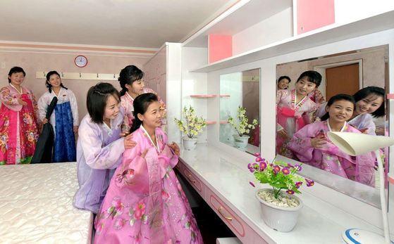 김정숙평양제사공장 여성 노동자들이 올해 1월 완공한 노동자 합숙소(기숙사)의 방에 걸려 있는 거울을 쳐다보고 있다. [사진=조선의 오늘]