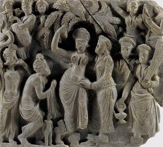 룸비니 동산의 사라수 나무의 가지를 붙들고 마야 왕비가 왕자를 낳고 있다.