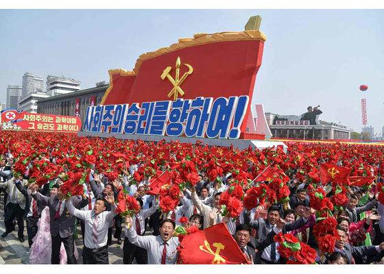 15일 김일성광장에서 열린 군중대회에서 평양 주민들이 노동당 기와 꽃술을 들고 환호하며 행진하고 있다. [노동신문]