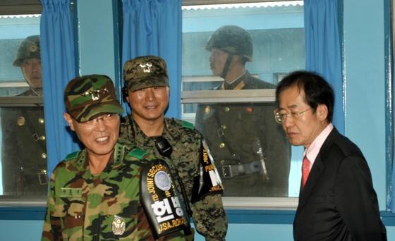 2011년 당시 홍준표 한나라당 대표가 국회 국방위원회의 국정감사 현지 시찰 일정으로 판문점 공동경비구역(JSA)의 군사정전위 회의실을 둘러보고 있다.창밖에서는북한군 병사들이 지켜보고 있다. [사진 중앙포토]
