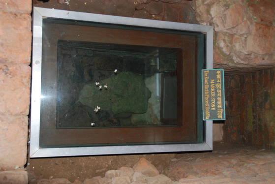 마야 데비 사원 안 붓다가 태어난 자리에 2200년 전 아소카왕 때 표시했다는 마커 스톤. 유리관 위로 순례객들이 떨어뜨린 꽃잎들이 보인다.