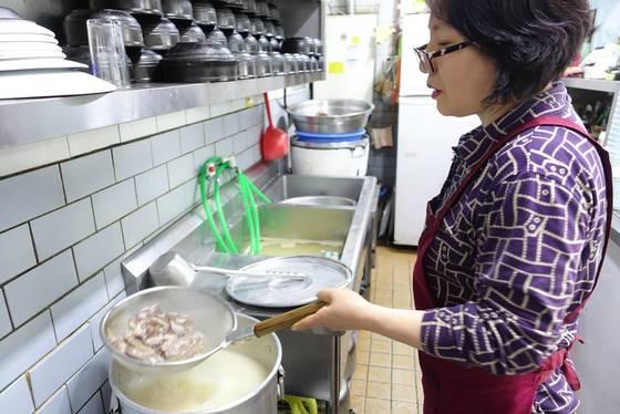 김미자씨가 끓고 있는 설렁탕 국물에 수육으로 나갈 고기를 데치고 있다.