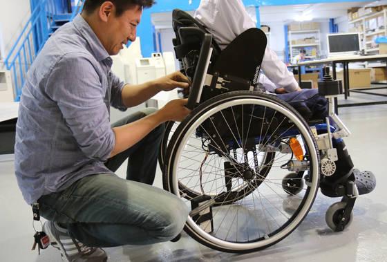 심재신 토도웍스 대표가 한 아이의 수동 휠체어에 토도드라이브를 장착하고 있다. [사진 토도웍스]