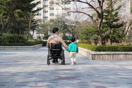 """토도드라이브를 수동 휠체어에 장착한 한 남성 고객이 """"딸의 손을 잡고 걸을 수 있게 돼 고맙다""""며 심재신 대표에게 전달한 사진. [사진 토도웍스]"""