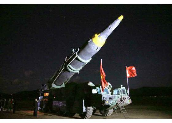 시험발사를 위해 '화성-12'의 발사대를 김정은이 지켜보는 가운데 세우고 있다. [사진=노동신문]