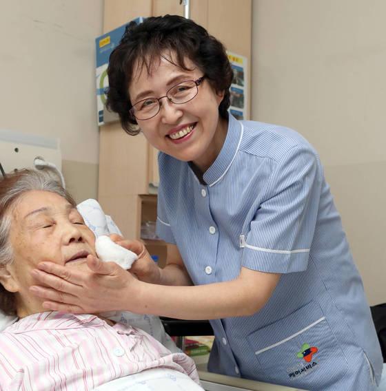 다솜이재단 직원 정윤숙 간병인(오른쪽)이 12일 건국대병원 공동 간병실에서 환자의 얼굴을 닦아주고있다. 이 회사 간병인은 입사 2년이 지나면 정규직으로 전환된다. 정씨는 정규직 7년차다. [최정동 기자]
