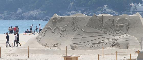 '2016 해운대 모래축제'를 찾은 시민과 관광객들이 대형 모래조각 작품을 구경하고 있다.