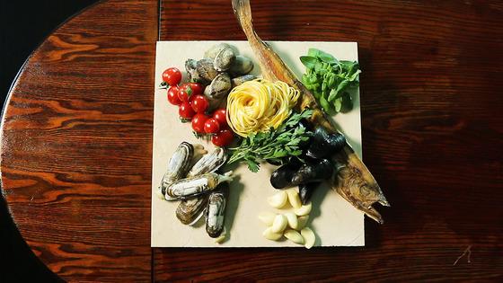 황태 딸리올리니에 들어가는 재료. 오른쪽 위부터 시계방향으로 바질, 황태, 홍합, 마늘, 가리맛조개, 방울토마토, 바지락. 가운데 면이 딸리올리니이고 그 옆이 이탈리안 파슬리.