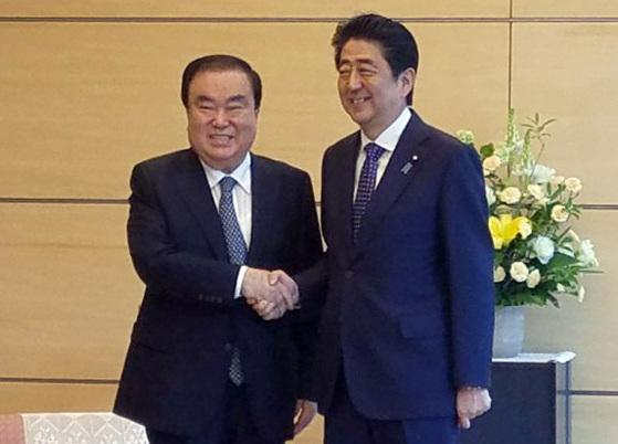 문희상 일본 특사가 18일 도쿄 총리관저에서 아베 신조 총리와 악수하고 있다. [도쿄=연합뉴스]